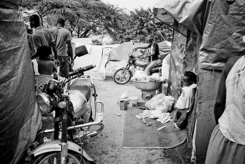 A man rides a motorcycle through a tent camp for people displaced by the earthquake on February 21, 2010 in Port-au-Prince, Haiti.