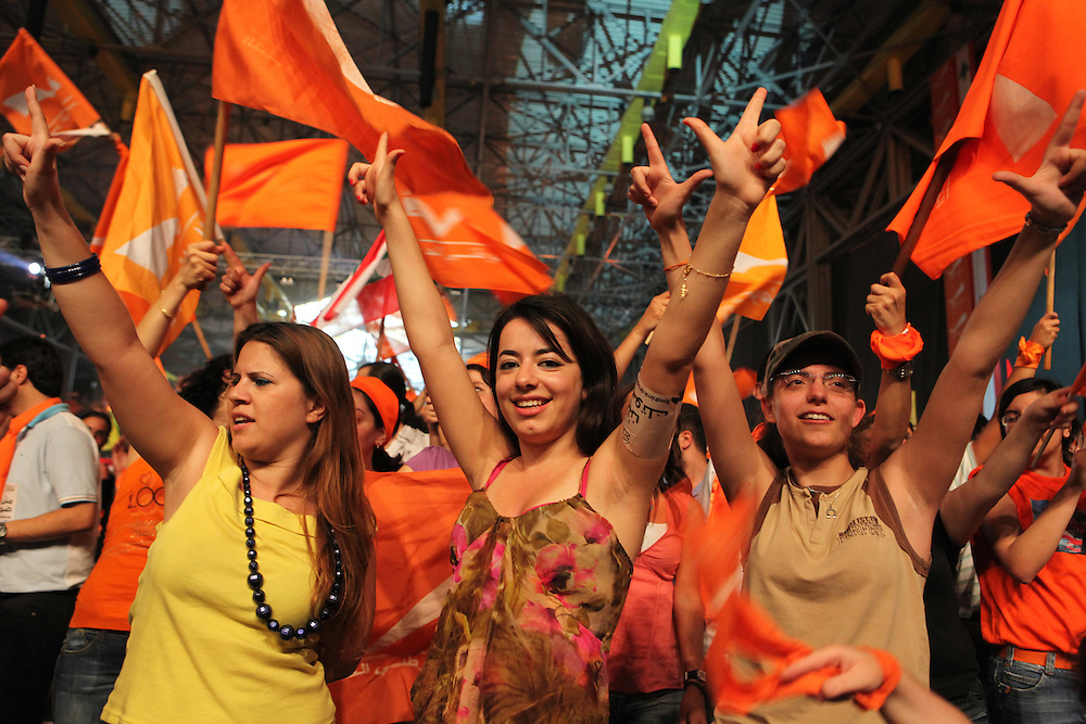 Former Lebanese General Michel Aoun's Free Patriotic Movement held a rally in Beirut just eight days before parliamentary elections. The 7 June elections are expected to be highly contested, with the governing pro-American March 14 coalition facing pressure from the Hizballah-led March 8 opposition, which Aoun's Free Patriotic Movement is a member of. The rally focused on Lebanon's Metn district just north of Beirut. Metn is expected to be one of the closest races between the Christian parties of both coalitions, as well as independent candidates. ///Supporters of Michel Aoun's Free Patriotic Movement dressed in the party's trademark orange color cheer and wave party flags, as well as Lebanese and other flags belonging to the various groups in the March 8 coalition, including Hizballah. Some make their fingers into a check mark, the logo of the FPM.