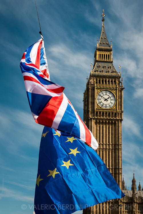 A british and a EU flag in front of the Big Ben in Parliament Square.