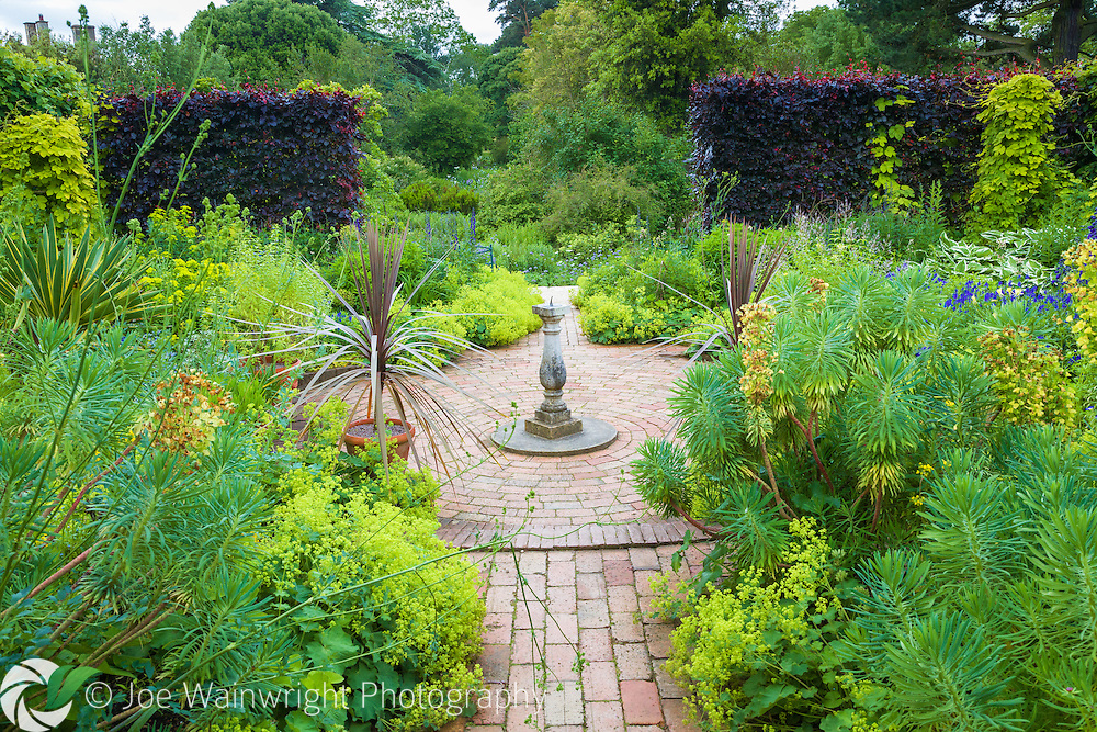 A sundial, euphorbias and bronze cordylines are key features of Mrs Winthrop's Garden at Hidcote Manor Garden, Gloucestershire.