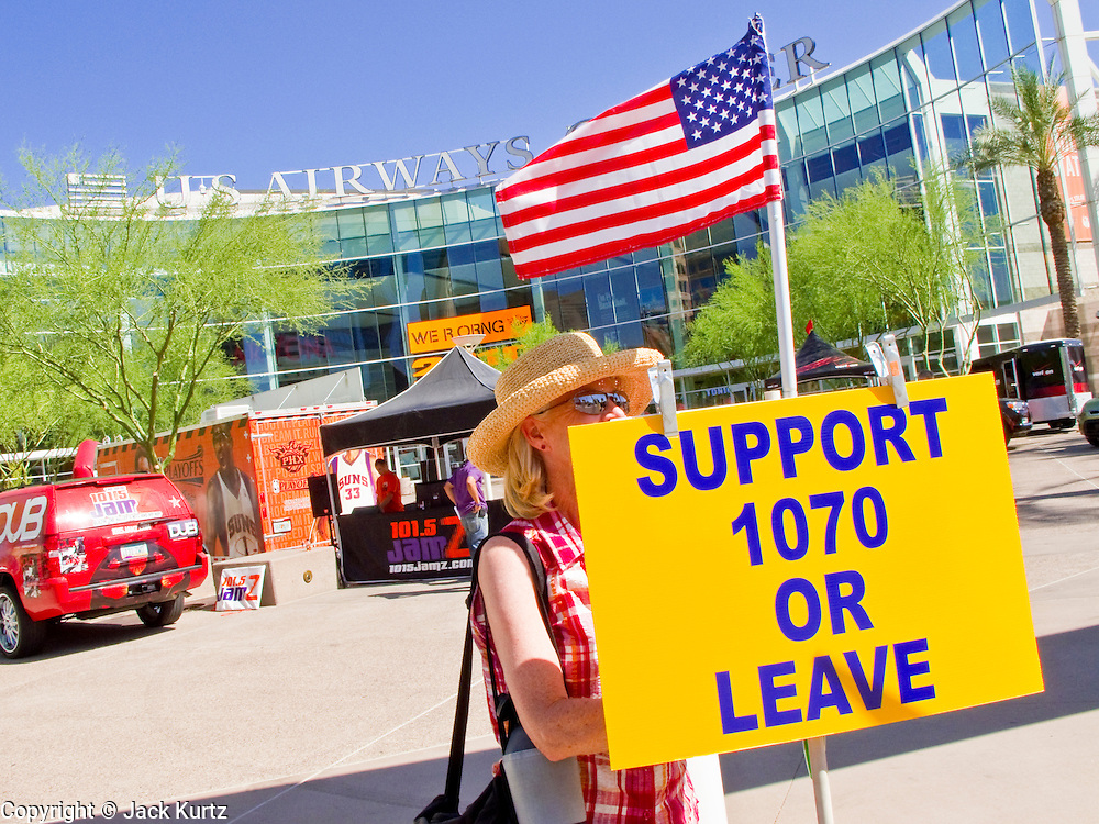 25 MAY 2010 - PHOENIX, AZ: A woman carries an American flag while she pickets the entrance to US Airways Arena, Tuesday, May 25. People opposed to illegal immigration and in favor of Arizona SB1070 picket the Phoenix Suns playoff game against the Los Angeles Lakers Tuesday. About 10 people attended the protest. One person opposed to SB1070 held a counter demonstration. SB1070 makes it an Arizona state crime to be in the US illegally and requires that immigrants carry papers with them at all times and present to law enforcement when asked to. PHOTO BY JACK KURTZ