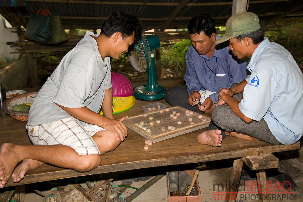 young people playing a board game.<br /> Mekong river Delta,  Vietnam, Asia