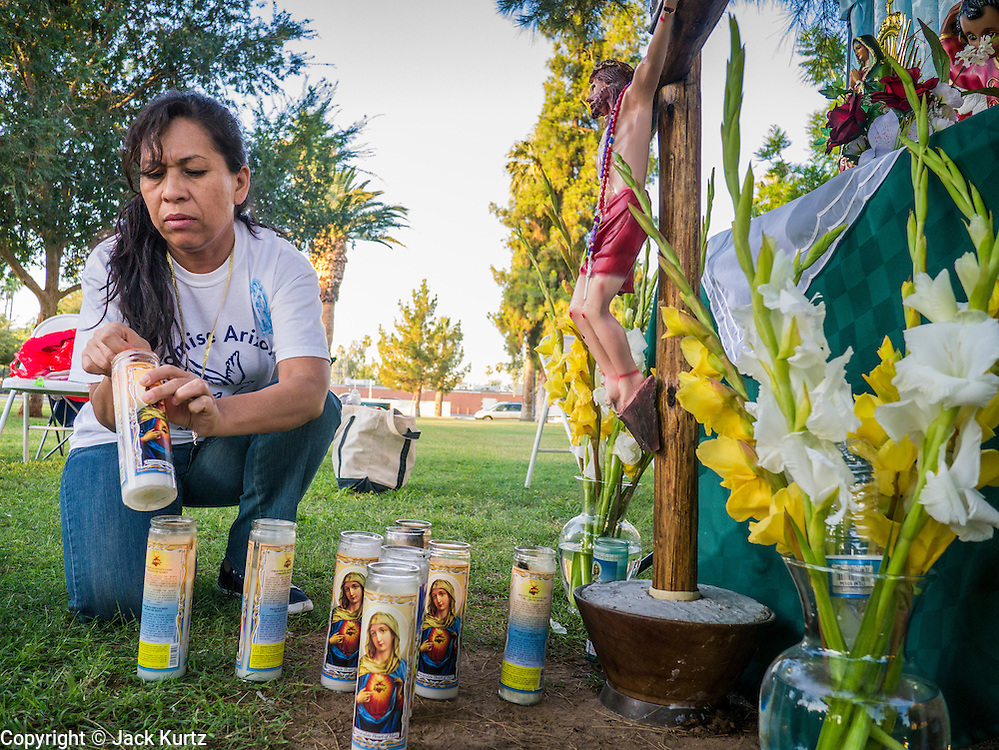 21 JUNE 2012 - PHOENIX, AZ:  A woman lights votive candles before saying the rosary at the Arizona State Capitol Thursday. About 40 people, members of the immigrant rights' group Promise AZ (PAZ), gathered at the Capitol in Phoenix Thursday to wait for the US Supreme Court decision on SB 1070, Arizona's controversial anti-immigrant law, in the case US v. Arizona. The court's ruling is expected sometime later this month. Members of PAZ said they would continue their vigil until the ruling was issued.        PHOTO BY JACK KURTZ