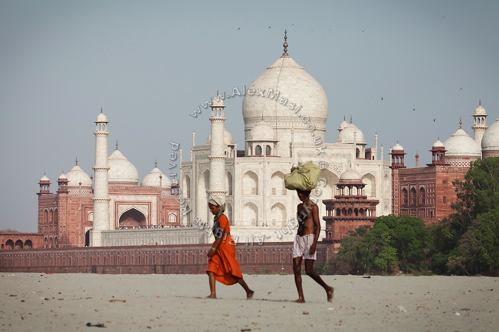 Two people are walking on the sands created by the low summer flow of the heavily polluted Yamuna River, across a view of the Taj Mahal, in Agra.