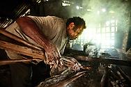 Village baker lighting twigs to start his oven. Village of Wintua, South West Bay, Malekula, Vanuatu