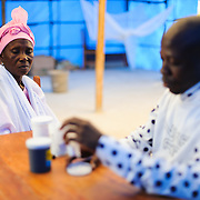 Isata, the mother of a schizophrenic patient, Mohammed, who lives in an abandoned taxi, receiving medication for her son from Ahmadu Jalloh, manager of the mental health program at the Wellbody Alliance clinic.