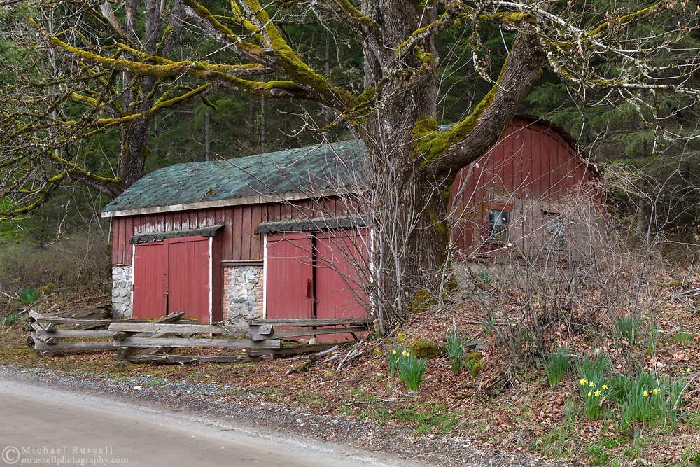 Barrel-roof shed  built between 1900 and 1910  by Richard Maxwell on his farm near Burgoyne Bay on Salt Spring Island, British Columbia, Canada.  The farm land is now part of Burgoyne Bay Provincial Park.  This shed was built for storage of larger farm equipment and has two, large access doors on the roadside of the building.  Photographed from Burgoyne Bay Road.
