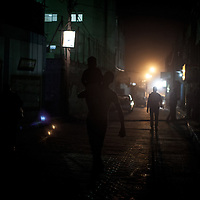 A man carring a child on his shoulder in a dark street of Al Shate'. Un uomo porta un bambino sulla spalla in una strada buia di Al Shate'.
