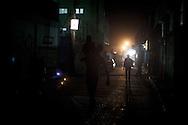 A man carring a child on his shoulder in a dark street of Al Shate'. Un uomo porta un bambino sulla spalla in una strada buia di Al Shate'.