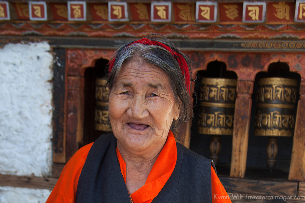 Asia, Bhutan, Thimpu. Bhutanese Woman and Prayer Wheels.