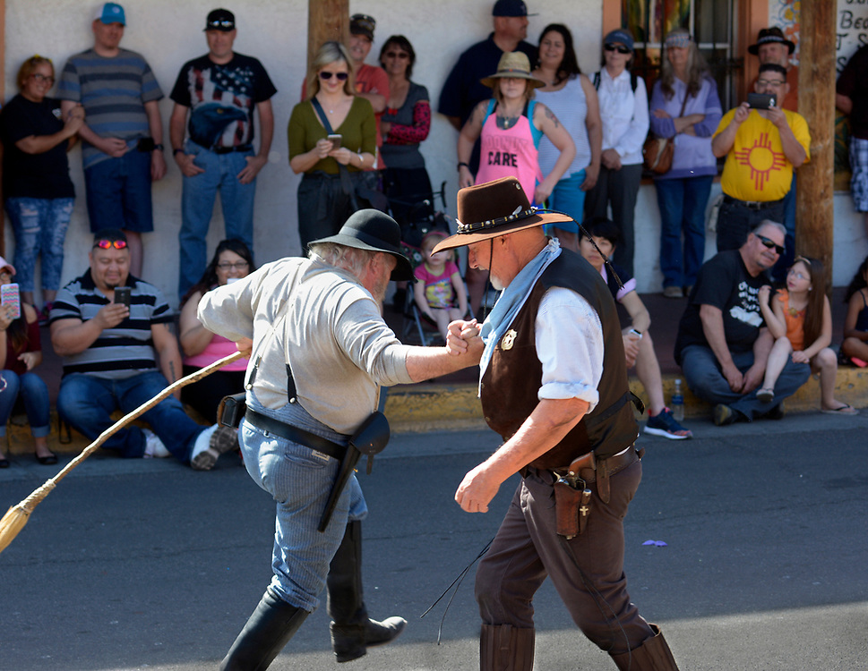 "gbs042317l/ASEC --Vistors to Old Town watch in the shade of a portal as New Mexico Gunfighters Dennis Britton of Albuquerque as ""Sarge,"" left, and Tommy Sims of Albuquerque as ""V Luna""  perform in the skit ""Cowboy Dress Up"" on Sunday, April 23, 2017. The New Mexico Gunfighters perform on the 2nd and 4th Sundays from March to October. (Greg Sorber/Albuquerque Jounal)"