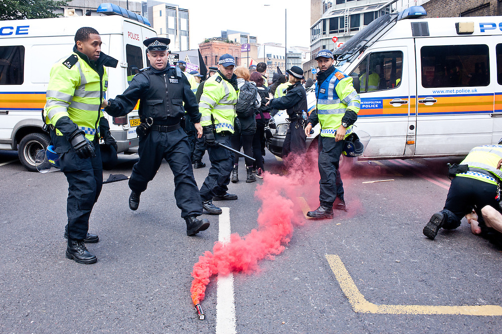 London, UK - 7 September 2013: a police officer runs towards a smoke pot as anti-EDL protester try to break the police line.