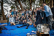 O-hanami, cherry blossom viewing, is arguably the biggest social event in Japan.  Companies reserve spots in Ueno Park months in advance.  Often an underling in a company will be sent to hold the space until the company workers can catch up later.  Food is in abundance and drink flows.  Here one such company poses for a group photo after consuming a fair amount of spirits.  Ueno Park, Tokyo, Japan.