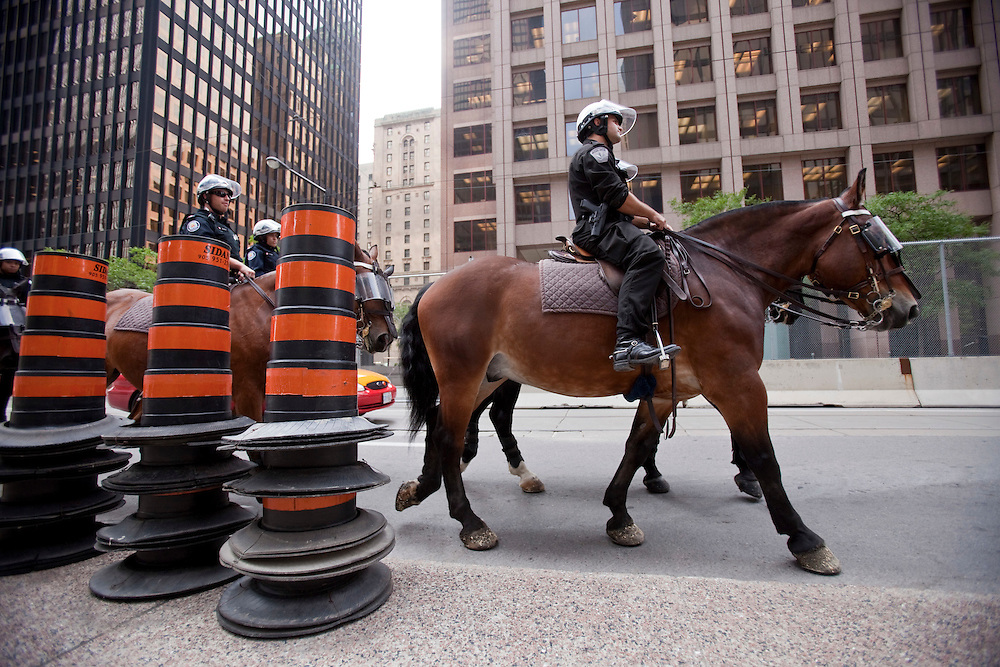 Police on horseback patrol the nearly deserted streets in the financial district of Toronto, Canada, June 25, 2010 where most office workers were told to work from home Friday, as the city prepares to host the G20 leaders this weekend.<br /> AFP/GEOFF ROBINS/STR