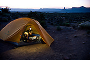 Snug in their tent, mountain bikers Katie Cavicchio and Brad Barlage review the next day's ride on a map, at a campsite on Utah's White Rim Trail in Canyonlands National Park.