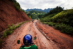 Motorbike riders drive on a muddy track in mountainous area of Son La Province, Vietnam, Southeast Asia.