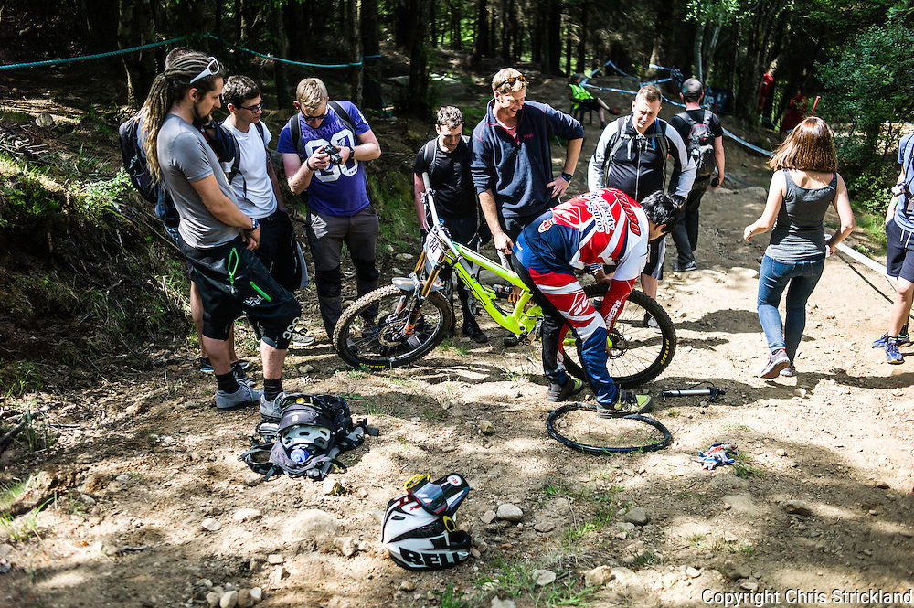 Nevis Range, Fort William, Scotland, UK. 3rd June 2016. All hands to the pump as Emanuel Pombo of Portugal fixes a puncture on track side. The worlds leading mountain bikers descend on Fort William for the UCI World Cup on Nevis Range.