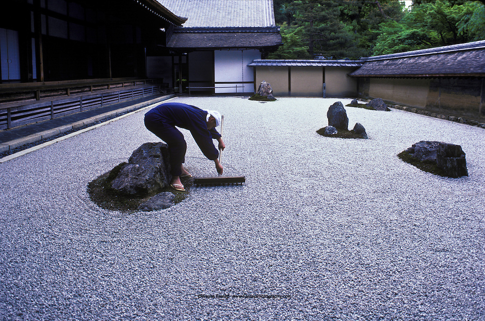 Seventeen year old Tadaichi Iwahashi, apprentice monk rakes the zen garden at Ryoanji, a Zen temple in Kyoto.  The rock and sand garden embodies Japanese aesthetics-nature at its simplest, art at  its most refined. Japan