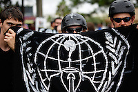 Protesters hold a flag in front of their faces at a rally by the Coalition to March on the RNC at Perry Harvey Park in Tampa, Florida on August 27, 2012.  The march is in response to the Republican National Convention which starts today in Tampa.  UPI/Matthew Healey