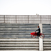 A surfer carries his surfboard on a bike in Fujisawa, Japan.
