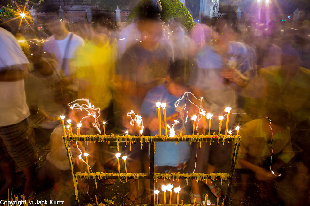 """25 FEBRUARY 2013 - BANGKOK, THAILAND:  Thais light candles and pray at Wat Benchamabophit Dusitvanaram (popularly known as either Wat Bencha or the Marble Temple) on Makha Bucha Day. Thais visit temples throughout the Kingdom on Makha Bucha Day to make merit and participate in candle light processions around the temples. Makha Bucha is a Buddhist holiday celebrated in Myanmar (Burma), Thailand, Cambodia and Laos on the full moon day of the third lunar month (February 25 in 2013). The third lunar month is known in Thai is Makha. Bucha is a Thai word meaning """"to venerate"""" or """"to honor"""". Makha Bucha Day is for the veneration of Buddha and his teachings on the full moon day of the third lunar month. Makha Bucha Day marks the day that 1,250 Arahata spontaneously came to see the Buddha. The Buddha in turn laid down the principles his teachings. In Thailand, this teaching has been dubbed the 'Heart of Buddhism'.     PHOTO BY JACK KURTZ"""