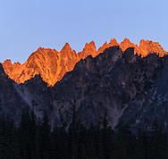 Alpenglow lights up Snagtooth Ridge behind a darkened Kangaroo Ridge at Washington Pass in the North Cascades of the Okanogan-Wenatchee National Forest in Washington State, USA.