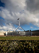 Australian Parliment House Canberra. View from the pond in late afternoon light of the front of Parliament House. Shot with an altered focus and a tilt and shift wide angler lens view from the garden in late afternoon light of the front of Parliament House.