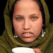 A green eyed Gujjar girl with a cup of salt tea. Lidderwat, Kashmir, India
