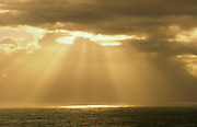 Storm clouds over ocean with sun rays breaking through; Hamakua Coast, Island of Hawaii.