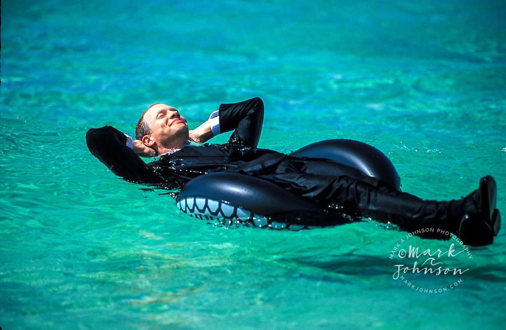 Australia, Queensland, happy businessman floating on inner tube on calm sea.  MR available.