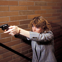 1987 New York City Police Detective Madeleine Lamorte poses in a staircase with her weapon drawn.