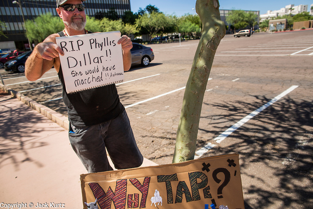 26 MARCH 2012 - PHOENIX, AZ:  BILL BOYLE, a comedy writer, holds up a sign in honor of Phyllis Diller during a topless protest march in Phoenix. About 40 people marched through central Phoenix Sunday to call for a constitutional amendment to give women the same right to go shirtless in public that men have. The Phoenix demonstration was a part of a national Topless Day of Protest. Phoenix prohibits women from going topless in public so protesters, women and men, covered their nipples and areolas with tape. The men did it to show solidarity with the women marchers.   PHOTO BY JACK KURTZ