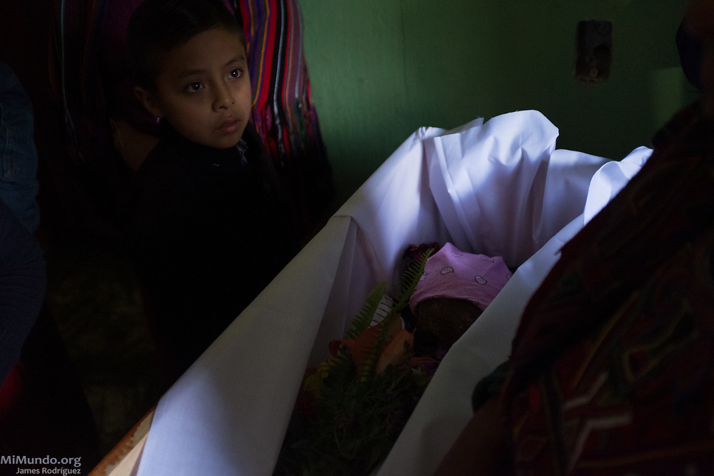 Family members watch as the remains of Jacinta Solis de Leon are arranged in a coffin. Ixil Mayan residents of Nebaj gather as the human remains of 36 war victims, including Solis de Leon's, are returned to their surviving family members for a proper burial. Most of the victims, exhumed from mass graves in Xe'xuxcap, near Acul, starved in the mountainside while fleeing State-led repression in 1982. Most of the remains, exhumed by members of the Forensic Anthropology Foundation of Guatemala (FAFG) in 2013, were identified using DNA analysis and buried 35 years after their death. Nebaj, Quiché, Guatemala. February 2, 2017.
