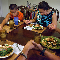 The Curry family, left to right, Antonio, 14, Ponce, 11, Evelyn and Lloyd, pray before dinner at their home on the military base at Fort Dix, N.J., Sept. 16, 2011.
