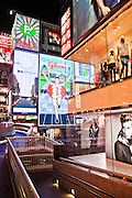 Pedestrians walk under neon and extreme signage incudling famous Glico Man in Dotonburi.
