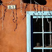 SHOT 12/26/2007 - Late afternoon light catches a window and Christmas lights on the side of a shop in Old Town Albuquerque. The area is a historic district in Albuquerque, New Mexico, dating back to the founding of the city by the Spanish in 1706. Today it is a popular shopping and tourist destination. Old Town comprises about ten blocks of historic adobe buildings grouped around a central plaza (a common feature of Spanish colonial towns). Many of the buildings in Old Town are houses that have been converted into restaurants and small art and souvenir shops. Albuquerque is the largest city in the state of New Mexico, United States. It is the county seat of Bernalillo County and is situated in the central part of the state, straddling the Rio Grande. The city population was 448,607 as of the 2000 U.S. census. As of the 2006 census estimate, the city's population was 504,949, with a metropolitan population of 816,811 as of July 1, 2006. In 2006, Albuquerque ranked as the 33rd-largest city and 61st-largest metropolitan area in the U.S. Albuquerque is home to the University of New Mexico (UNM) and Kirtland Air Force Base as well as Sandia National Laboratories and Petroglyph National Monument. The Sandia Mountains run along the eastern side of Albuquerque and the Rio Grande flows through the city north to south..(Photo by Marc Piscotty/ © 2007)