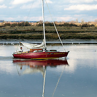 A lone sailor navigates the River Blackwater in  small red boat on a clear winter day