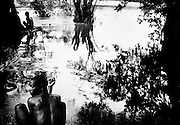 Men bathing in the river Mano, which marks the border between Sierra Leone and Liberia. Women and children were not allowed in the water, because several had been taken by crocodiles in the areas flooded when the river became swollen in the rainy season. The man in the background keeps watch while the other men bathe. <br /> June 2002.