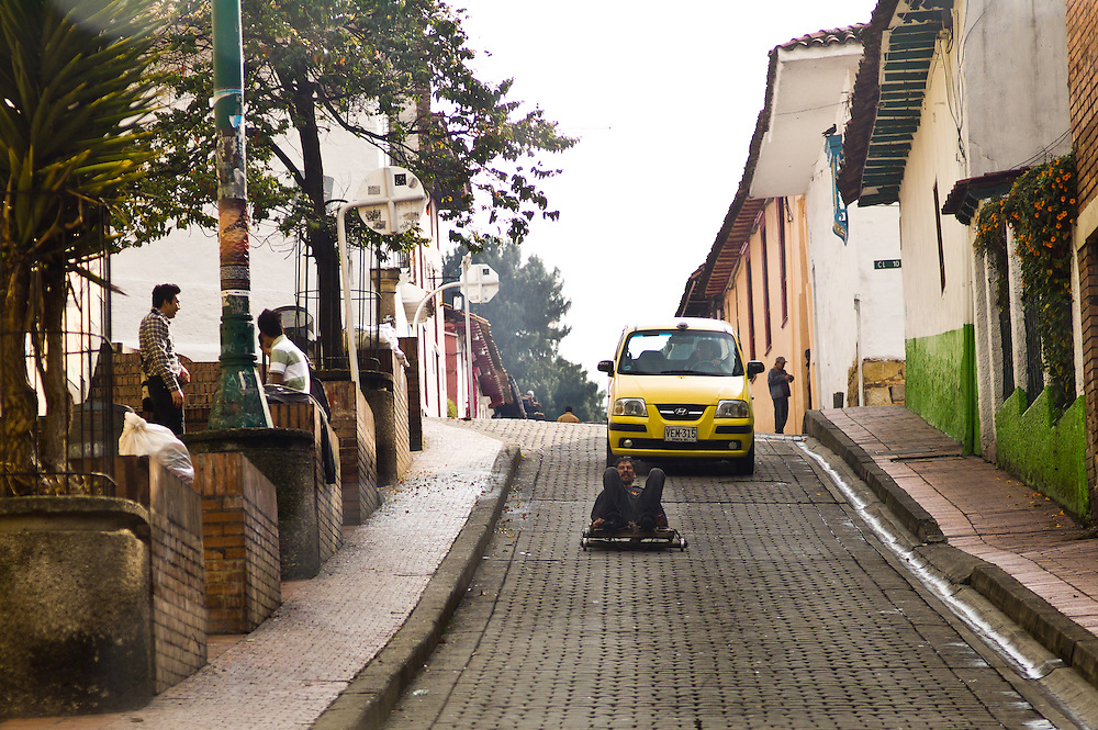 A man rides a cart down a steep hill in Bogotá, Colombia.