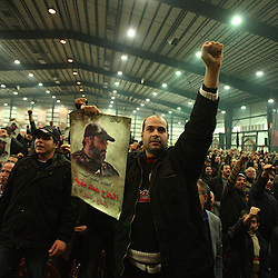 A man holds a poster of Imad Mugniyeh among a crowd of Hezbollah members and supporters paying their respects to the slain militant commander in Beirut, Lebanon on Feb. 14, 2008. Imag Mugniyeh was killed in a mysterious car bombing in Damascus, Syria. Mugniyeh a.k.a. Hajj Radwan, was among the most feared terror operatives in the world.