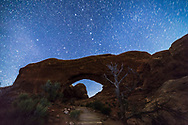 The Big Dipper and the Little Dipper turning around Polaris (at left) over the North Window Arch at Arches National Park, Utah, with a sky brightening with moonlight. A wash from an LED flashlight provided some foreground illumination. <br /> <br /> This is a stack of 4 x 45-second exposures with the Rokinon 14mm lens at f/2.8 and Canon 6D at ISO 3200.