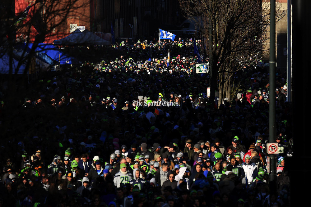 Thousands of fans walk next to CenturyLink Field during the Seattle Seahawks victory parade in Seattle Wednesday, Feb. 5, 2014. <br />