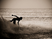 The silhouette of a surfer thrashes up a wave at Dreamland, Bali, Indonesia.