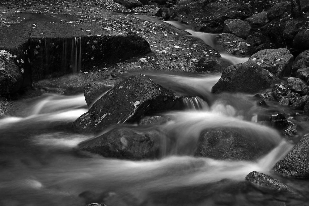 This intimate landscape photography image of Flume Brook at Franconia Notch State Park near Lincoln in the New Hampshire White Mountains region features silky water tumbling down the creek during New England fall foliage season. Table Rock is a small section of Conway granite in this New Hampshire State Park that was exposed and outcropped of hundreds of years. This scenic New Hampshire cascading water section is 500 feet long and 75 feet wide.<br />