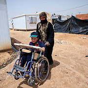 2015 April&mdash;Zaatari camp for Syrian refugees, Jordan. Against all odds, Khalid, 7, from Daraa, Syria, is the top student in his first grade class. This fortitudinous young man lost his mother at age three, he has been separated from his father for over two years by war, and he is physically disabled with muscular dystrophy. Khalid and his stepmother, Dilal, fled to Jordan for what they thought would be around a month stay&mdash;until the war quieted down. Due to the continued unrest in Syria they have lived in Zaatari camp for over two years.  <br /> <br /> Dilal walking Khalid to school.