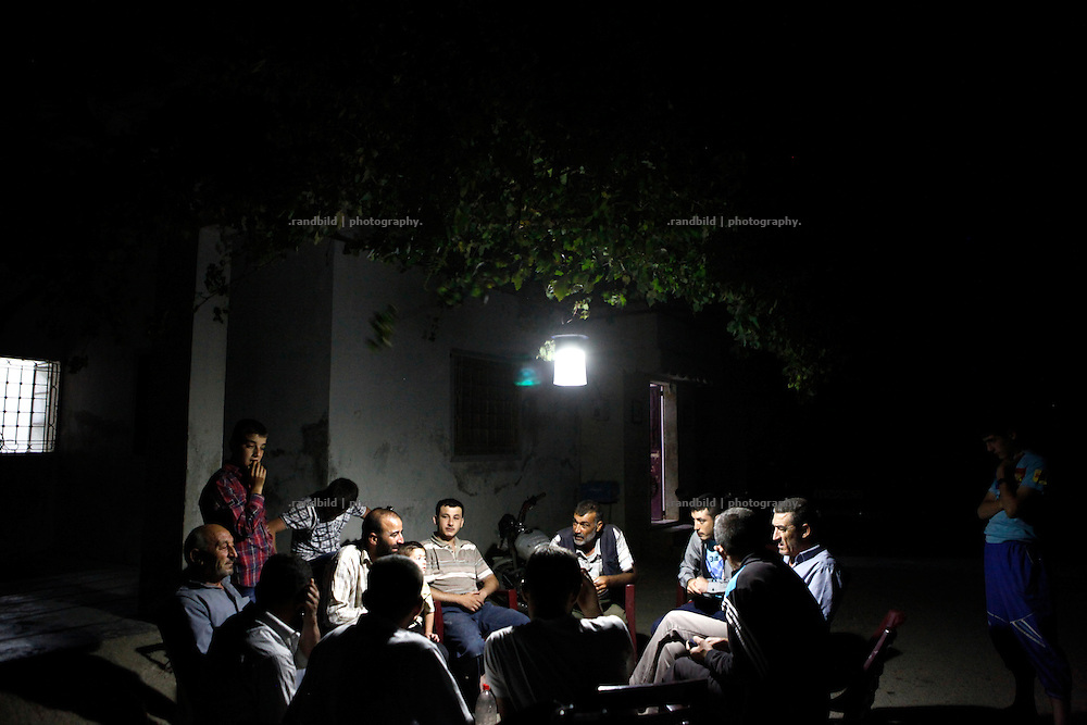 Several men of a neighbourhood sit together outside on a street in Koreen to enjoy the convenient summer evening chatting under a solar charged light hanging in tree branches.<br />