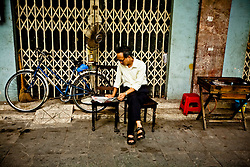 A Vietnamese man reads a newspaper in a street of Hanoi, Vietnam, Southeast Asia