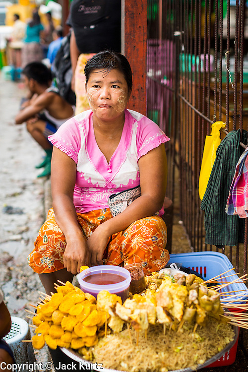 09 JUNE 2014 - YANGON, MYANMAR: A snack vendor in the San Pya Fish Market (also spelled Sanpya). San Pya Fish Market in Yangon is one of the largest wholesale fish markets in Yangon. The market is busiest in early in the morning, from before dawn until about 10AM.    PHOTO BY JACK KURTZ