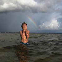 BRENDAN FITTERER     Times.PT_309902_FITT_rainbow (07/29/2009 PORT RICHEY) A rainbow decorates the dark horizon as Chase Fox (cq), 8, wipes salt water from his eyes while snorkeling with his parents in the Gulf Wednesday evening just west of Durney Key near the Pithlachascotee River. The shallow waters offer a close-up view of pinfish, crabs, and other marine life..BRENDAN FITTERER     Times
