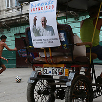 (091815  Havana, Cuba) A bicitaxi (bicycle taxi) with a poster welcoming Pope Francis passes by boys playing soccer in the street in Old Havana, Friday,  September 18, 2015. photo by Angela Rowlings.